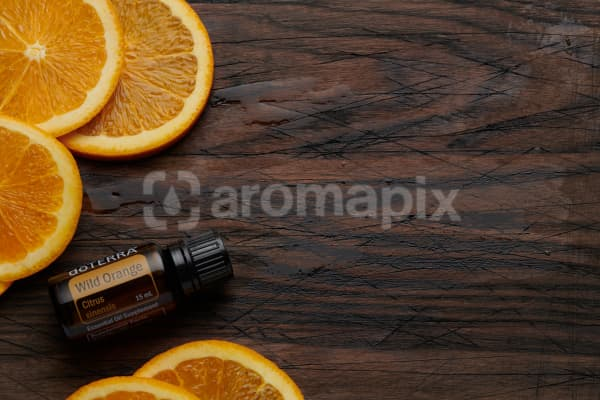 doTERRA Wild Orange oil and slices on rustic wooden chopping board.