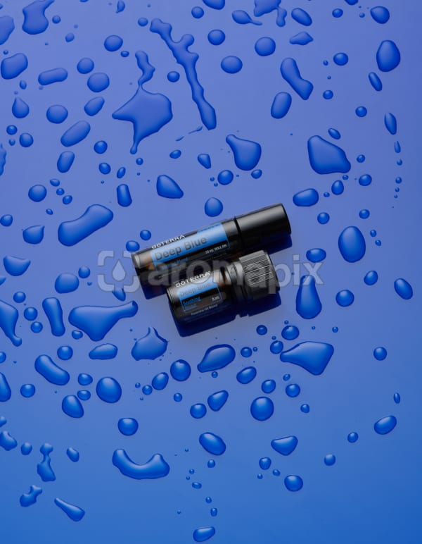 doTERRA Deep Blue Athletic Blend Roll On and Athletic Blend 5ml on blue perspex with water drops.