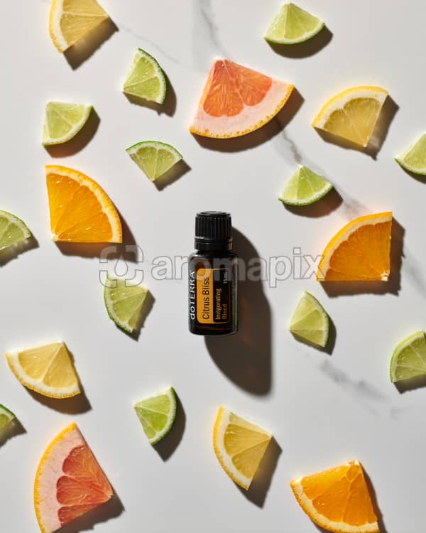 doTERRA Citrus Bliss essential oil blend and slices of citrus fruits on a white marble background.