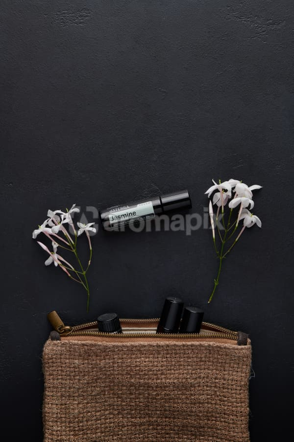 doTERRA Jasmine Touch with jasmine flowers and a clutch filled with roller bottles on a black concrete background.