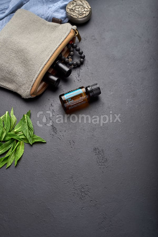 doTERRA AromaTouch with clutch, accessories and mint leaves on a black concrete background.