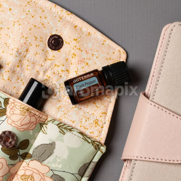 doTERRA Black Pepper on an essential oil bag with a diary on a gray textured background.