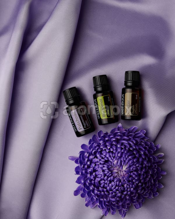 doTERRA Patchouli, Bergamot and Ginger with a purple Chrysanthemum on pale purple satin.
