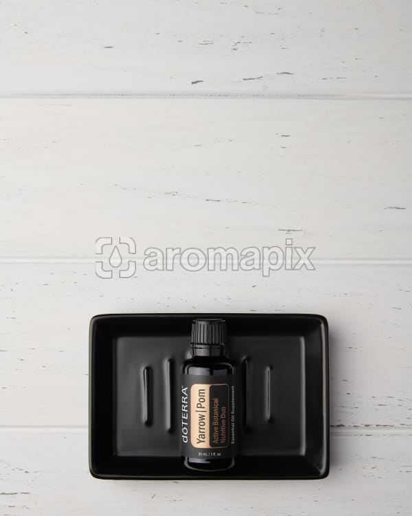 doTERRA Yarrow Pom in a black soap dish on a white wooden background.