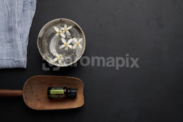 doTERRA Petitgrain in a wooden scoop with orange blosson flowers in a bowl of water on a black concrete backgrouns.