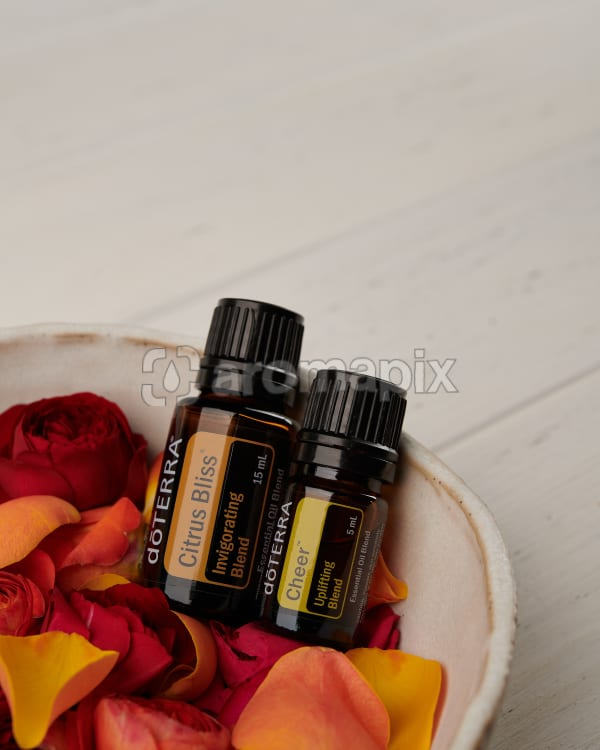 doTERRA Citrus Bliss and Cheer with roses and rose petals in a ceramic bowl on a white background.