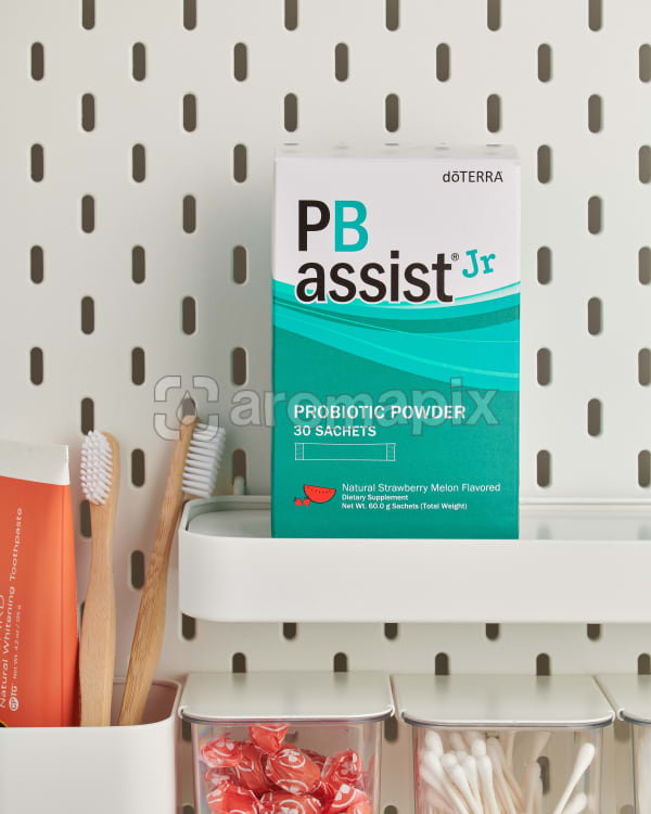 doTERRA PB Assist Jr on a bathroom shelf with additional doTERRA products and bathroom accessories.