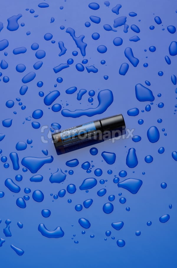 doTERRA Deep Blue Roll On on blue perspex with water drops.