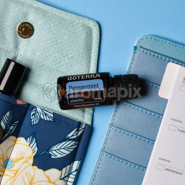 doTERRA Peppermint on an essential oil bag with a diary on a blue textured background.