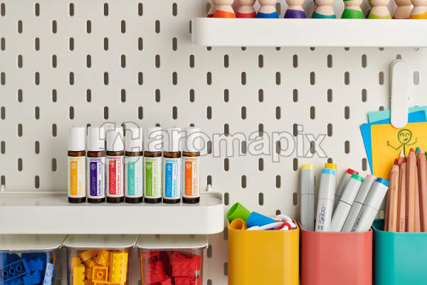 doTERRA Kids Collection of Thinker, Calmer, Stronger, Tamer, Steady, Rescuer and Brave lined up on a storage shelf surrounded by kids stationery and toys.