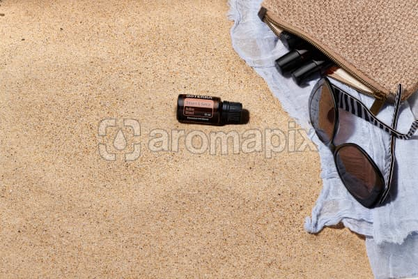 doTERRA Smart and Sassy with sunglasses, scarf and roller bottles in a clutch on the beach.