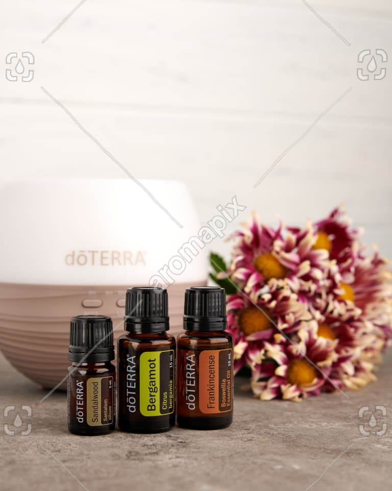 doTERRA Sandalwood, Bergamot and Frankincense with a dffuser and flowers on a bench