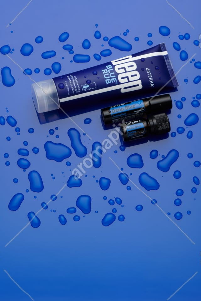 doTERRA Deep Blue products on blue with water