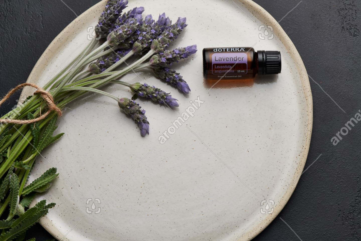 doTERRA Lavender and lavender flowers on white ceramic plate with black background