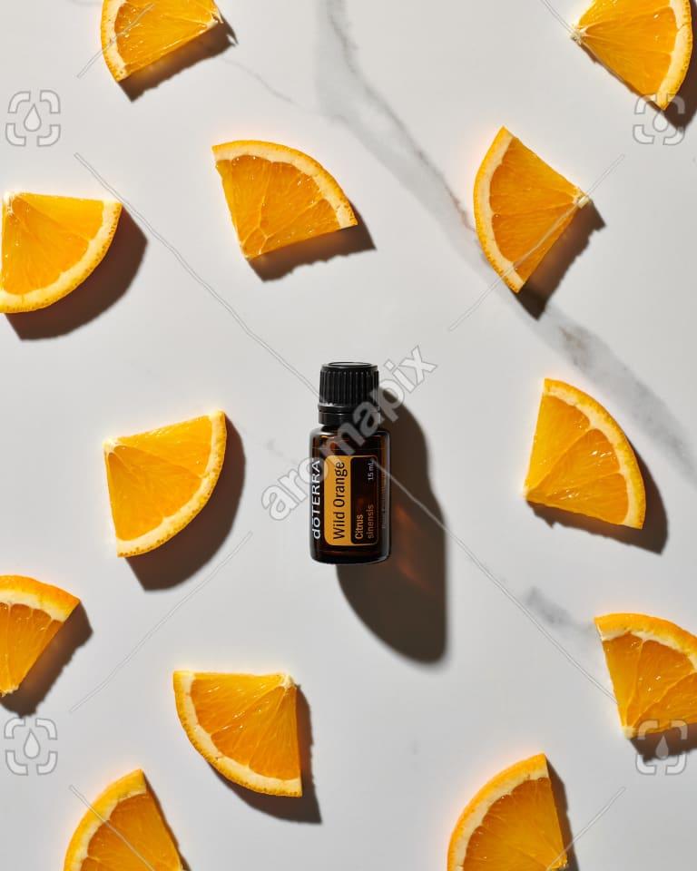 doTERRA Wild Orange essential oil and orange slices on white