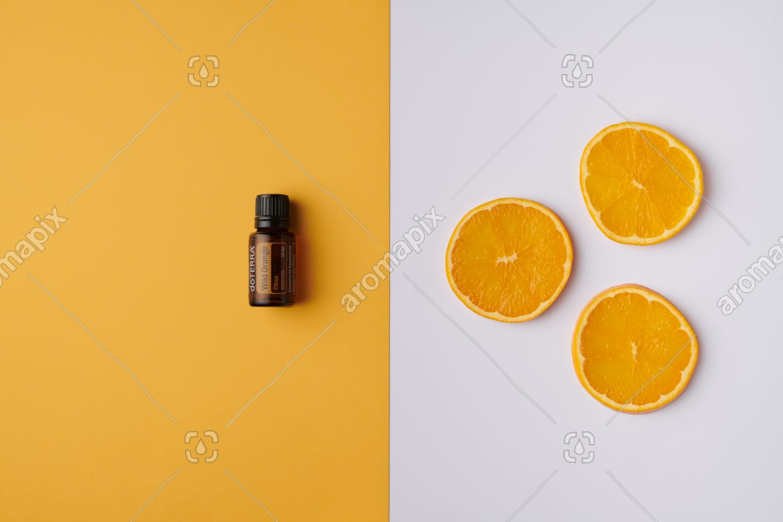 doTERRA Wild Orange product and slices on orange and white background