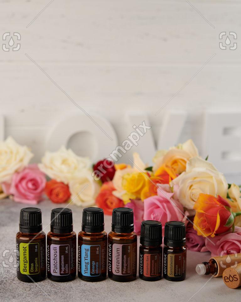 doTERRA Patchouli, Geranium, Ylang Ylang, Bergamot, Sandalwood and Cinnamon Bark with roller bottle on white