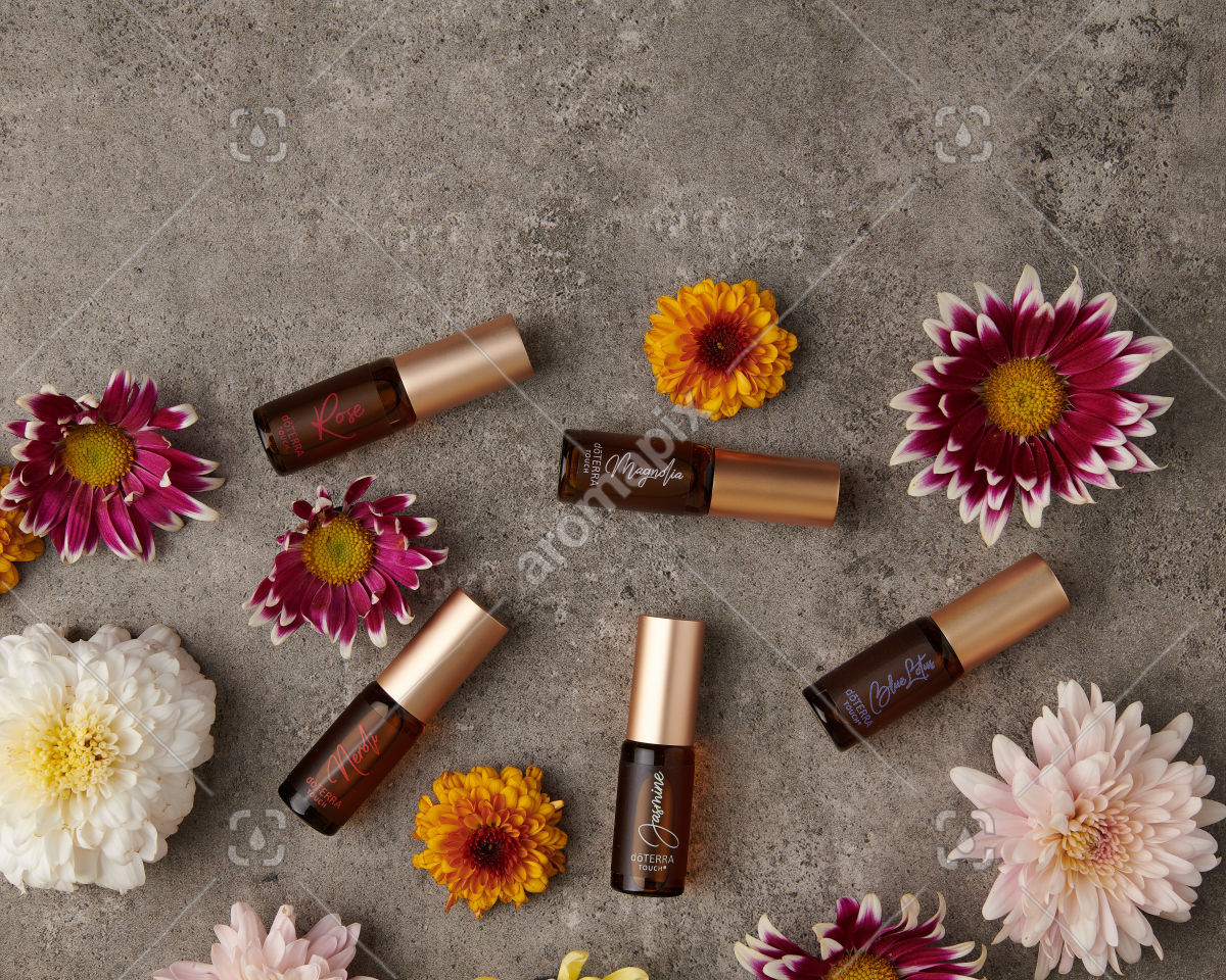 doTERRA Neroli Touch, Jasmine Touch, Rose Touch, Magnolia Touch and Blue Lotus Touch with flowers on gray