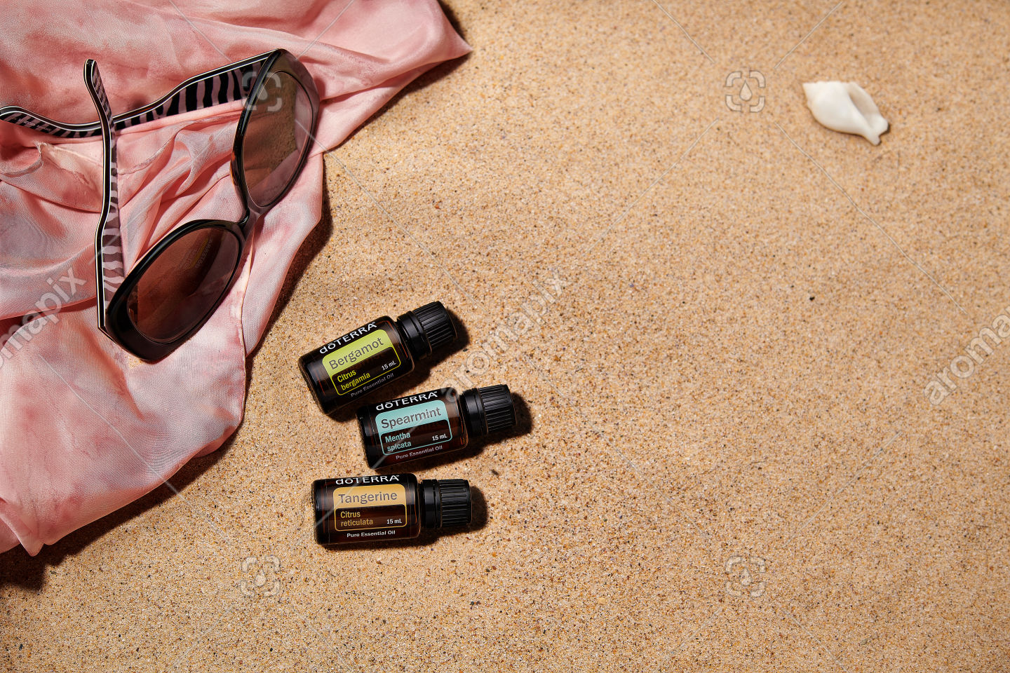 doTERRA Bergamot, Spearmint and Tangerine with accessories on sand