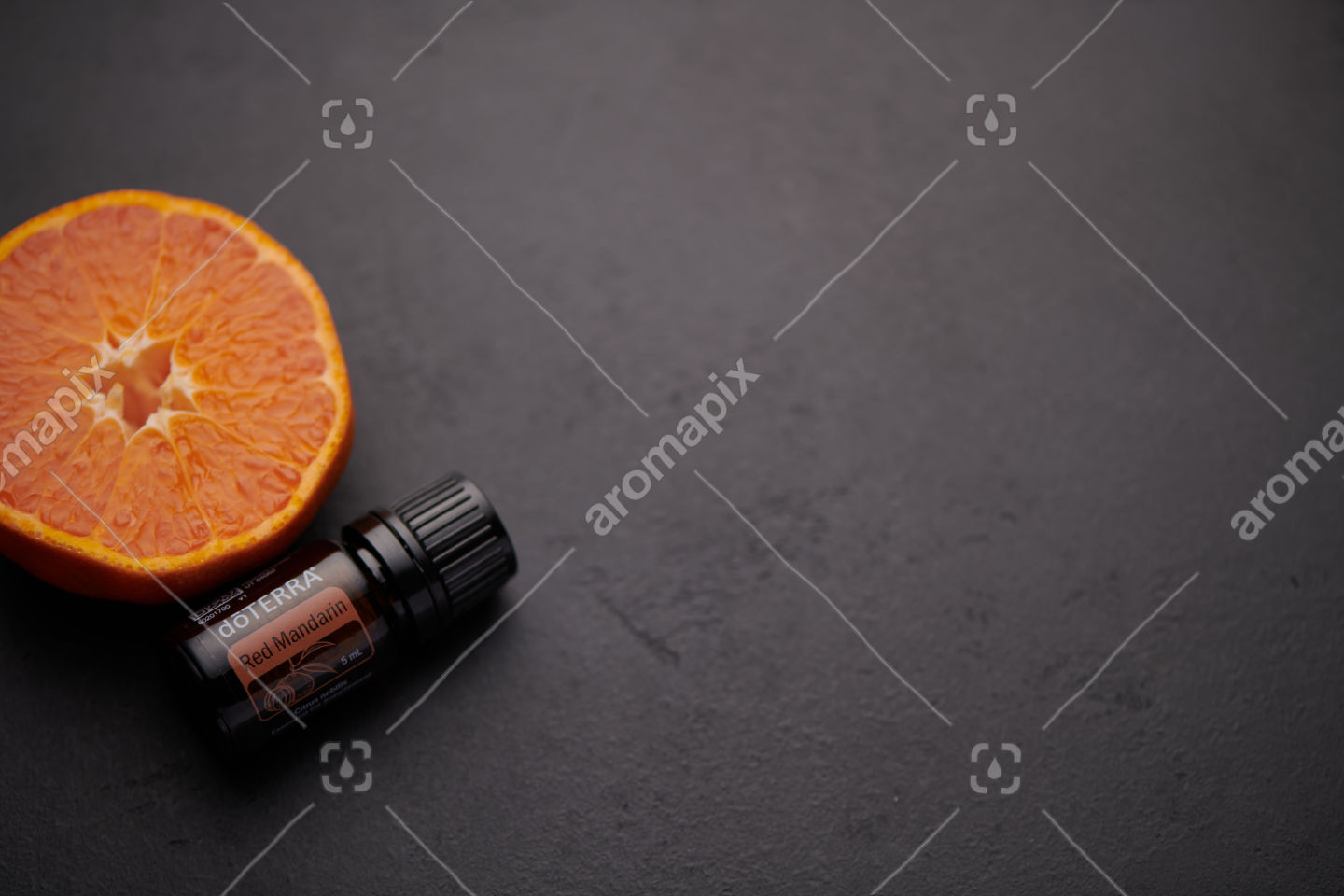 doTERRA Red Mandarin product and mandarin fruit on black background