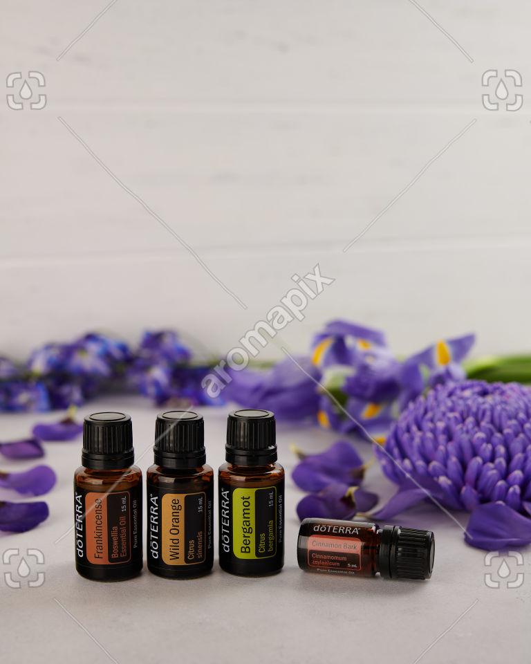 doTERRA Frankincense, Wild Orange, Bergamot and Cinnamon Bark with scattered purple flowers.