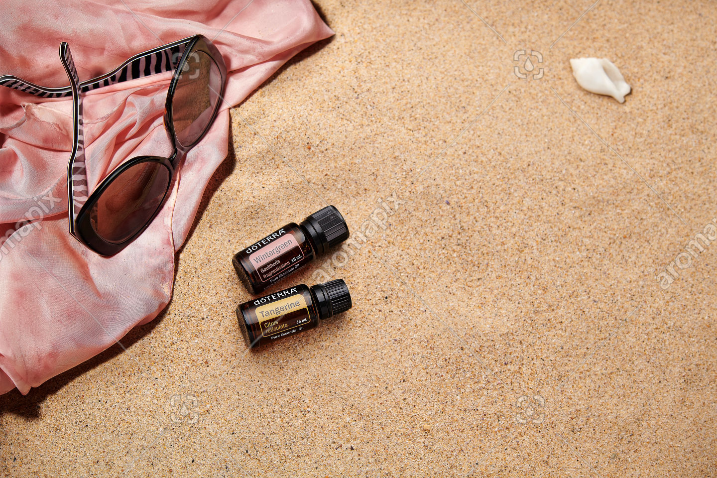 doTERRA Wintergreen and Tangerine with accessories on sand