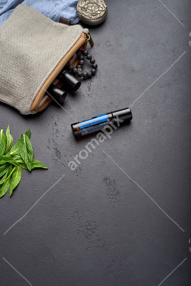 doTERRA Deep Blue Touch with mint leaves on black