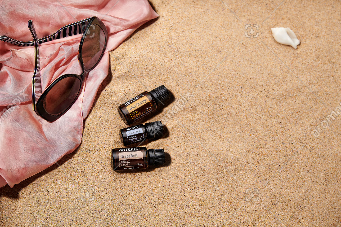 doTERRA Wild Orange, Juniper Berry and Grapefruit with accessories on sand