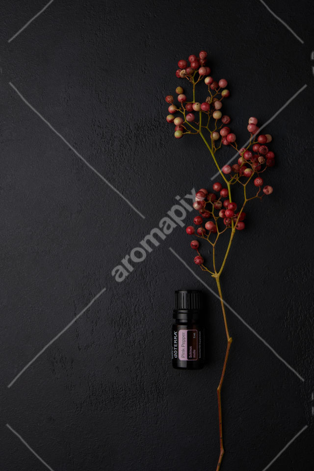 doTERRA Pink Pepper and pink peppercorn on black background