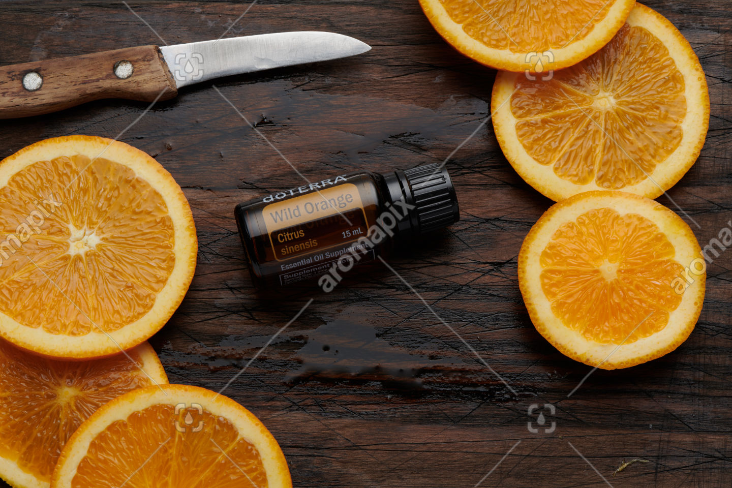 doTERRA Wild Orange product and slices on wooden board