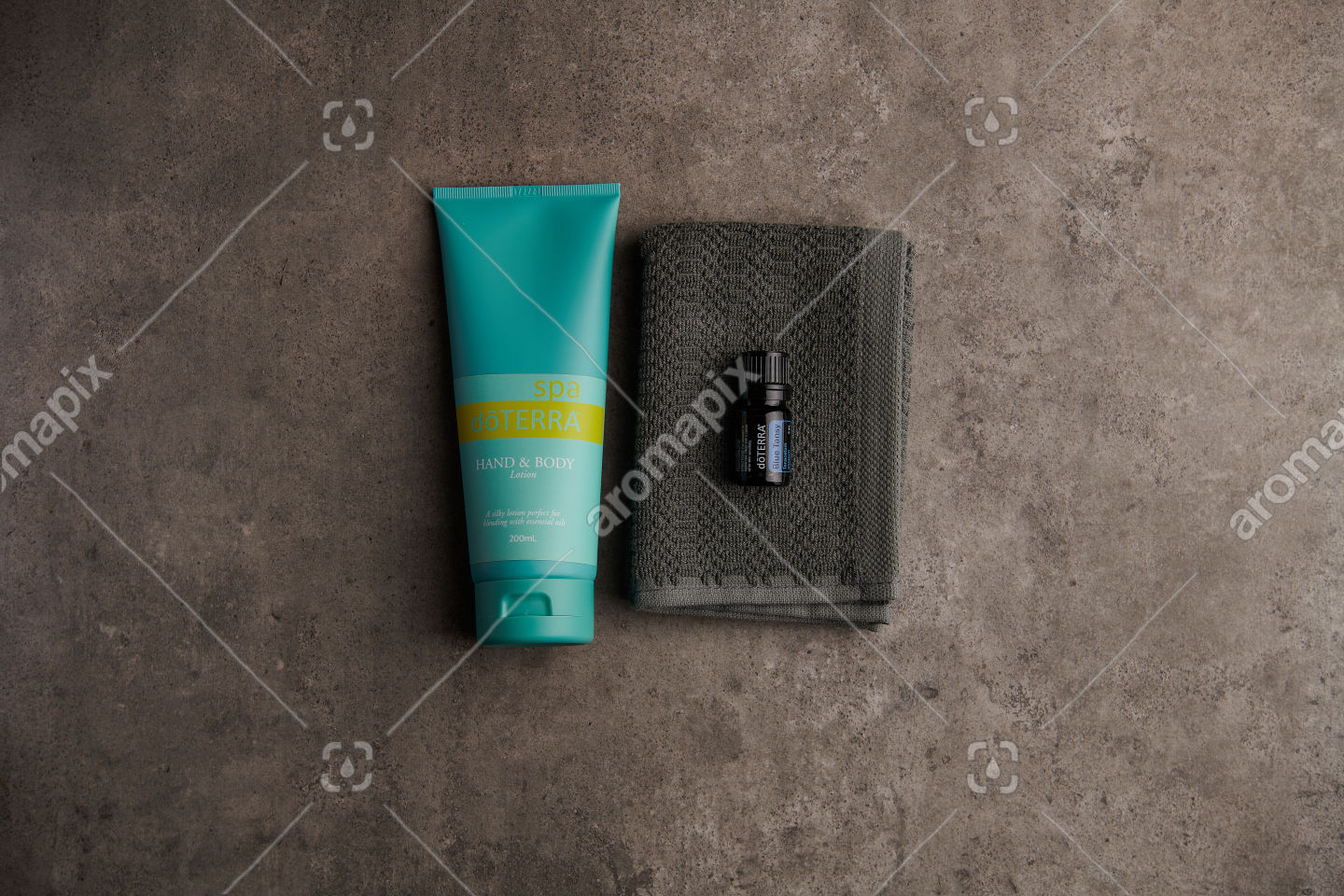 doTERRA Spa Hand and Body Lotion and Blue Tansy essential oil on stone