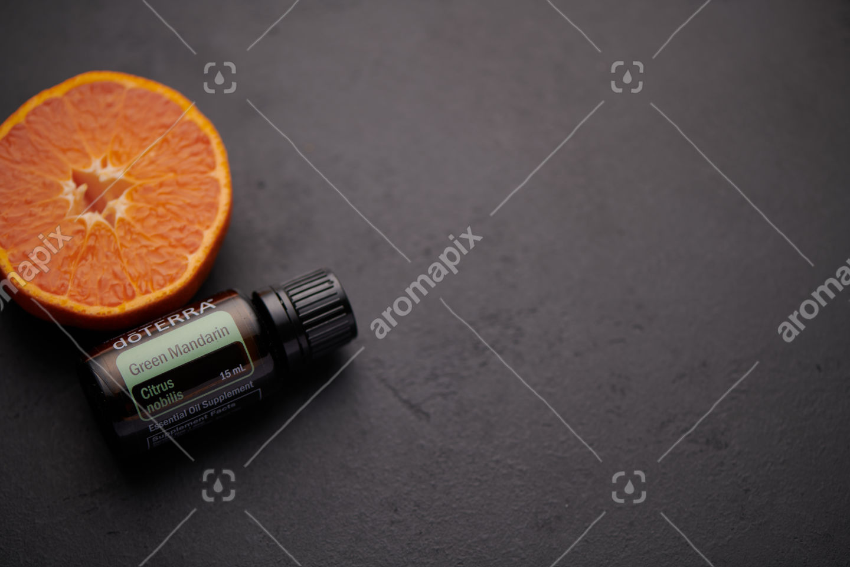 doTERRA Green Mandarin product and mandarin fruit on black background
