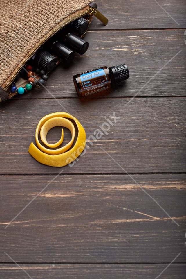 doTERRA Easy Air with lemon peel on wooden background