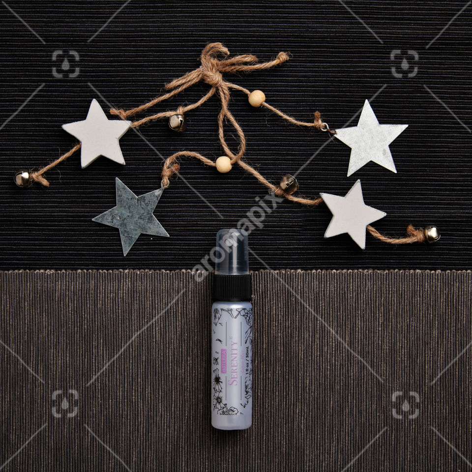doTERRA Serenity Linen Mist with holiday decorations on a textured background