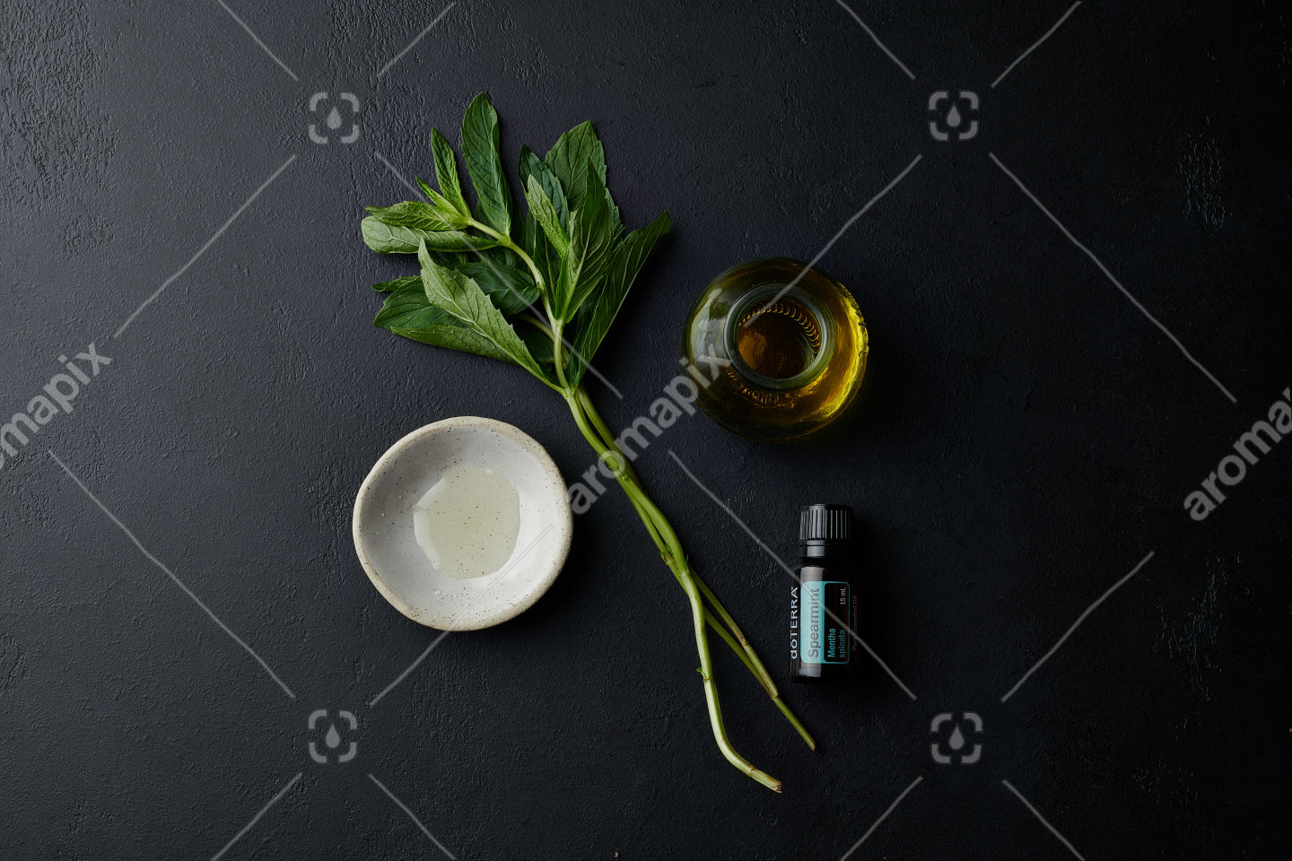 doTERRA Spearmint with utensils and a mint branch on black