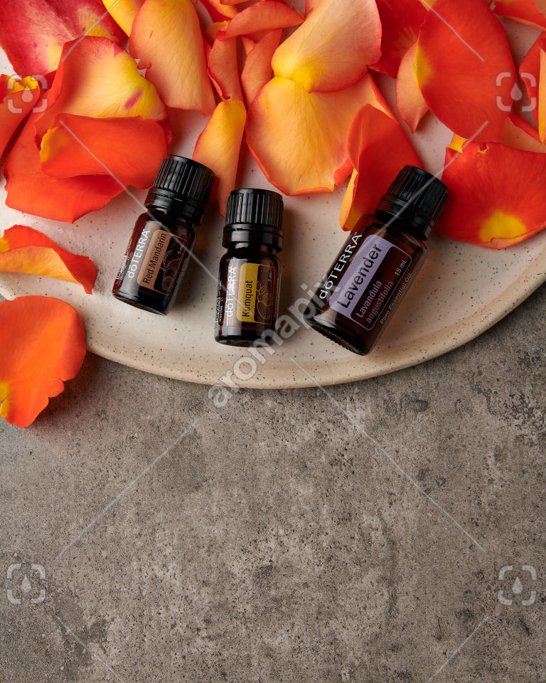 doTERRA Red Mandarin, Kumquat and Lavender with rose petals on gray