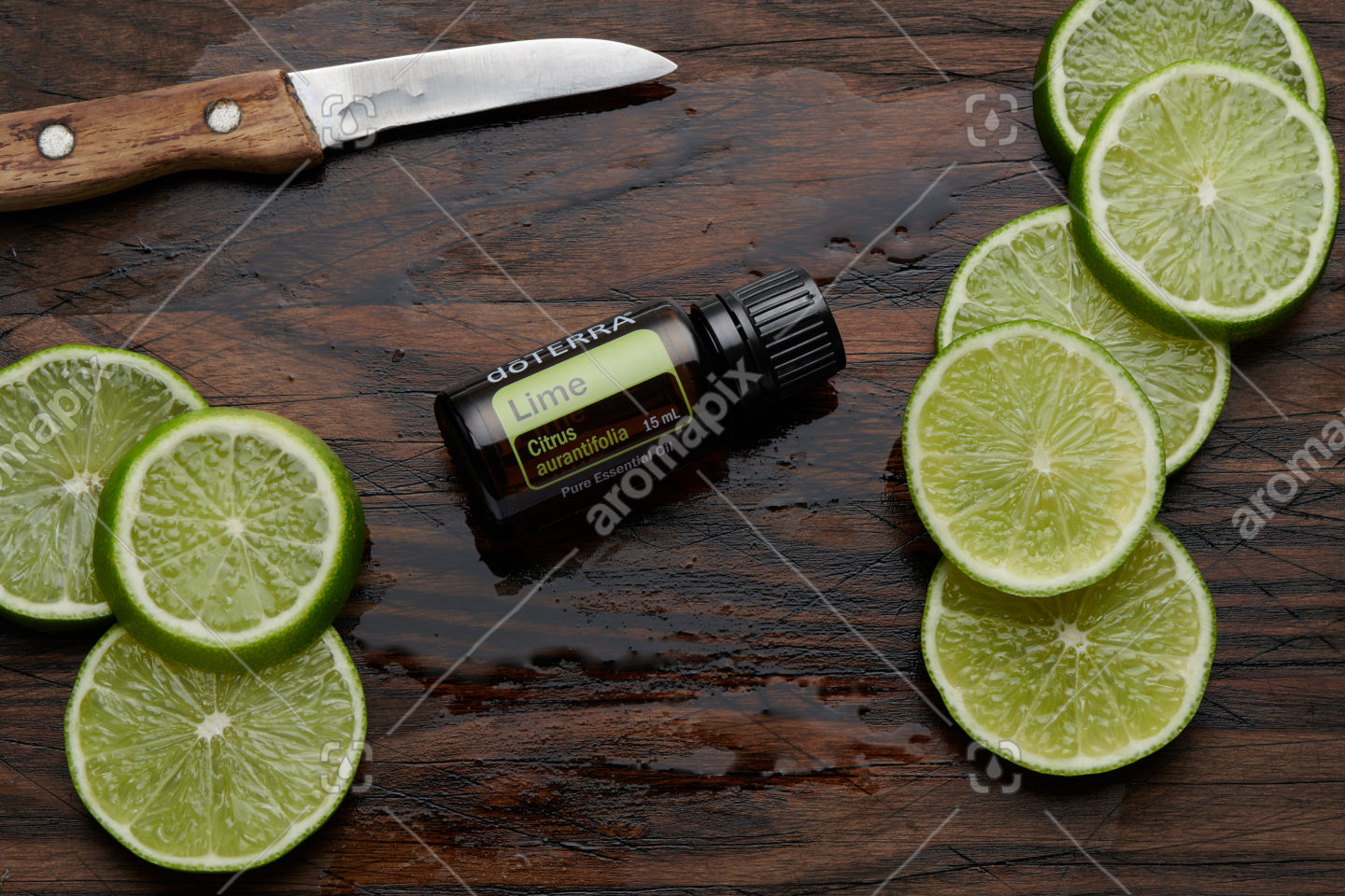 doTERRA Lime oil and lime slices on wooden board