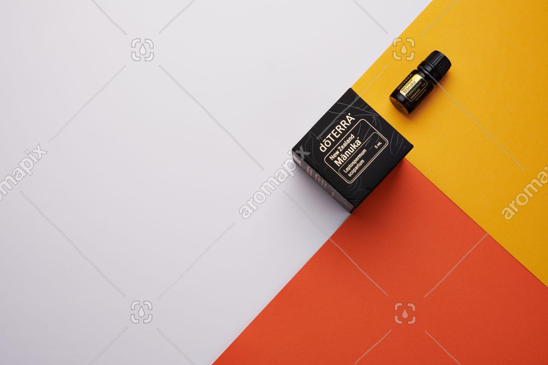 doTERRA Manuka and box on yellow, orange and white geometric background