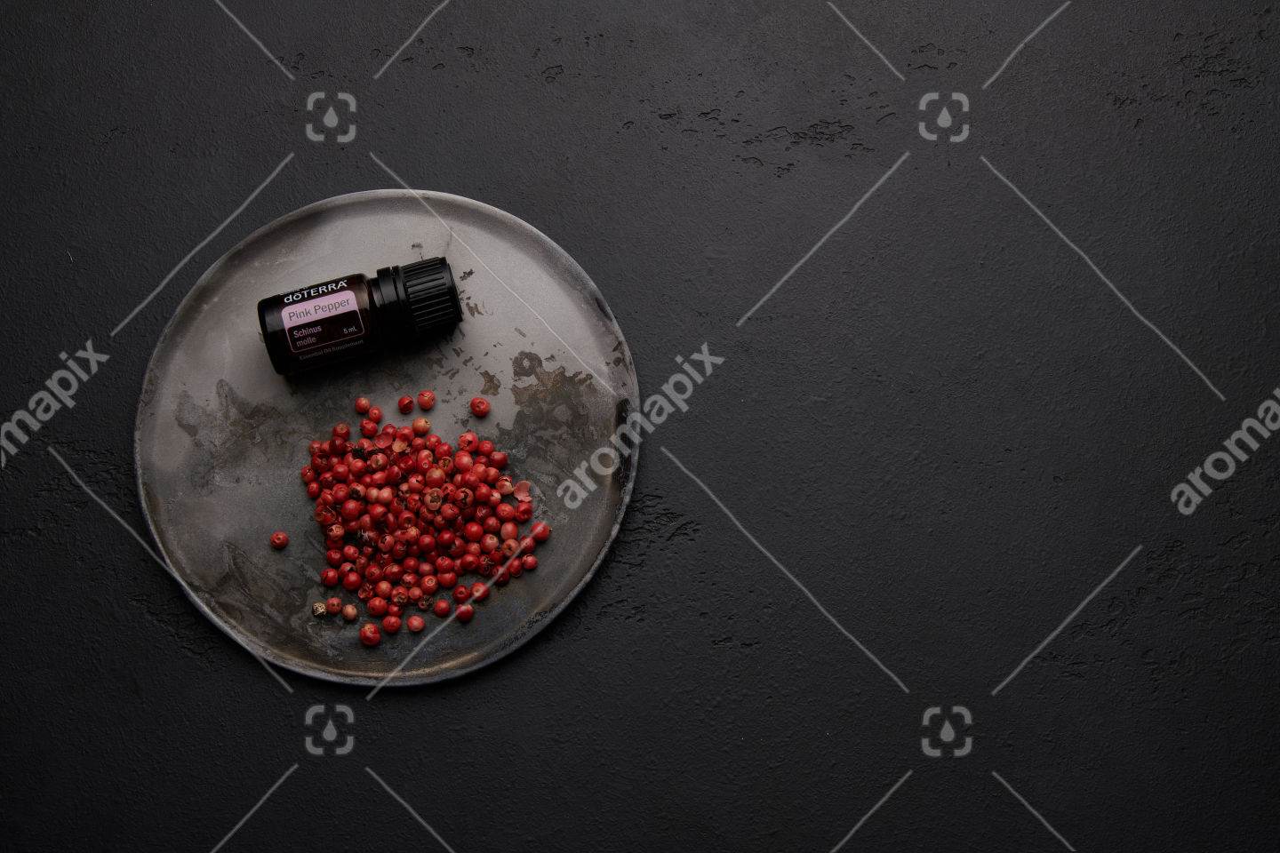 doTERRA Pink Pepper with pink peppercorns on black background