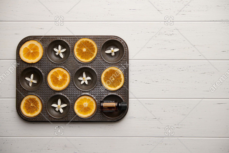 doTERRA Wild Orange with seville orange slices and orange blossoms on white