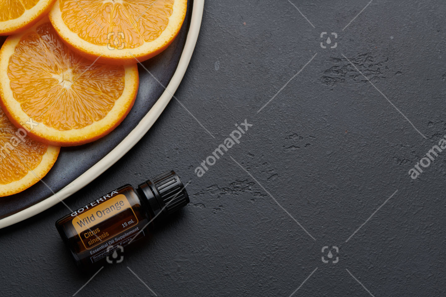 doTERRA Wild Orange product and slices on ceramic plate