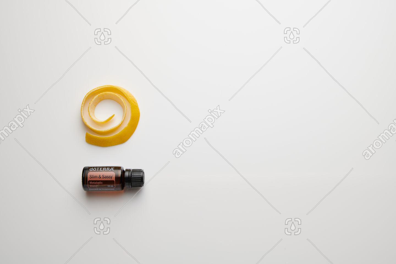 doTERRA Slim and Sassy with lemon peel on white perspex