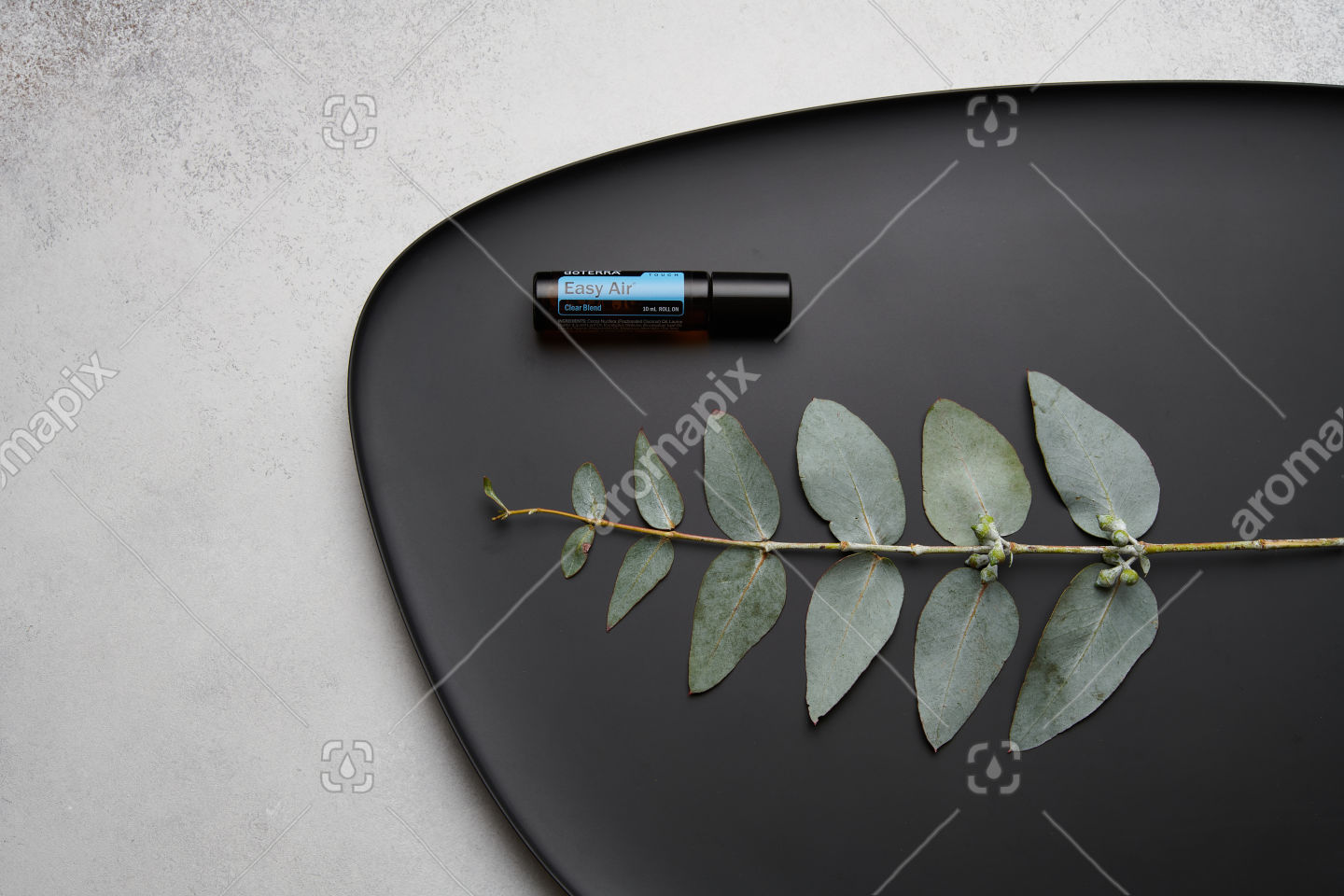 doTERRA Easy Air Touch and eucalyptus leaves on black plate