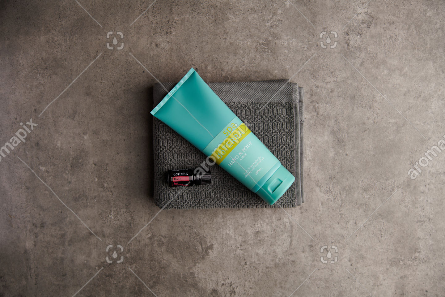 doTERRA Spa Hand and Body Lotion and Rose essential oil on stone