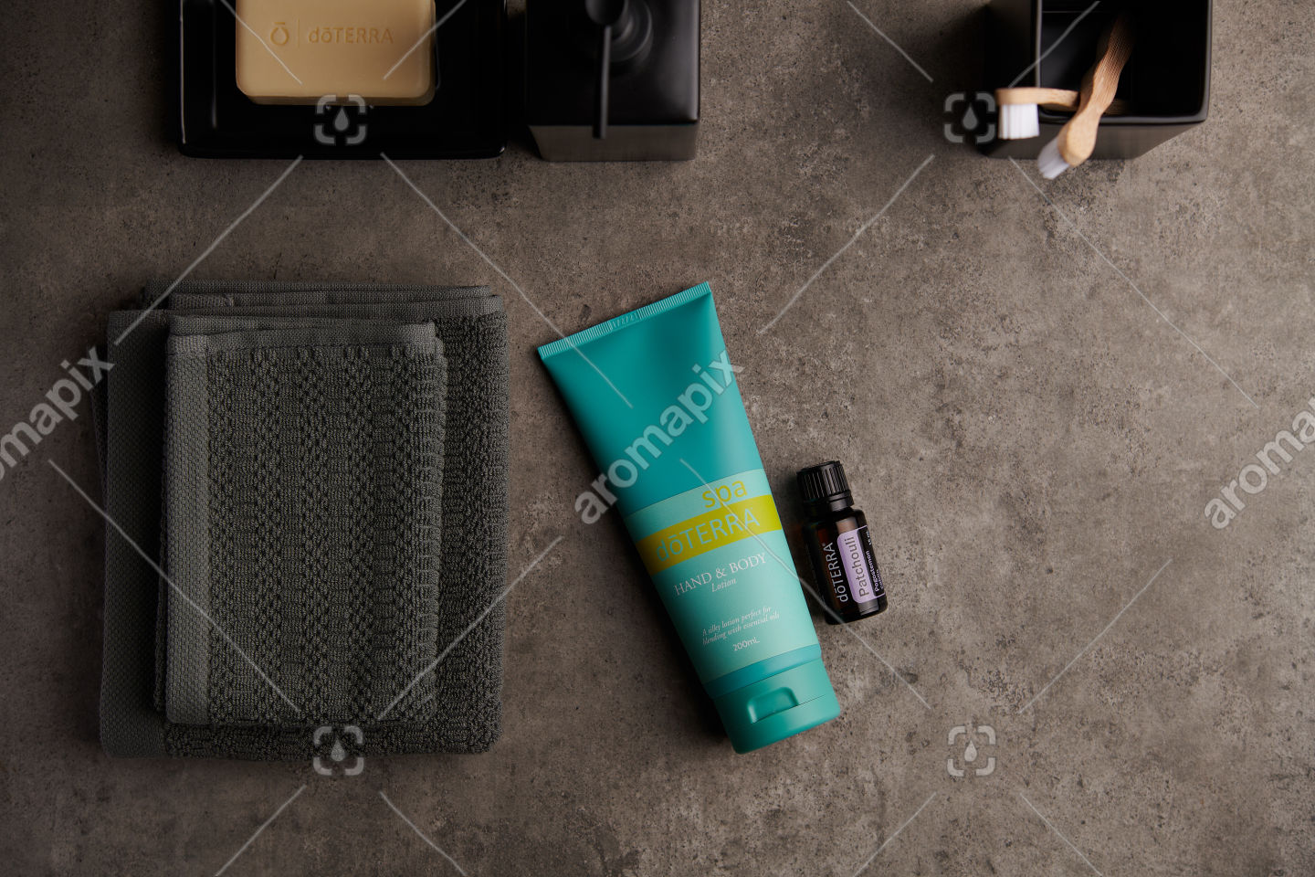 doTERRA Spa Hand and Body Lotion and Patchouli essential oil on stone