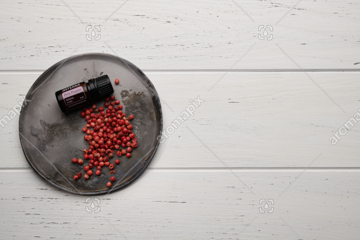 doTERRA Pink Pepper with pink peppercorns on white background
