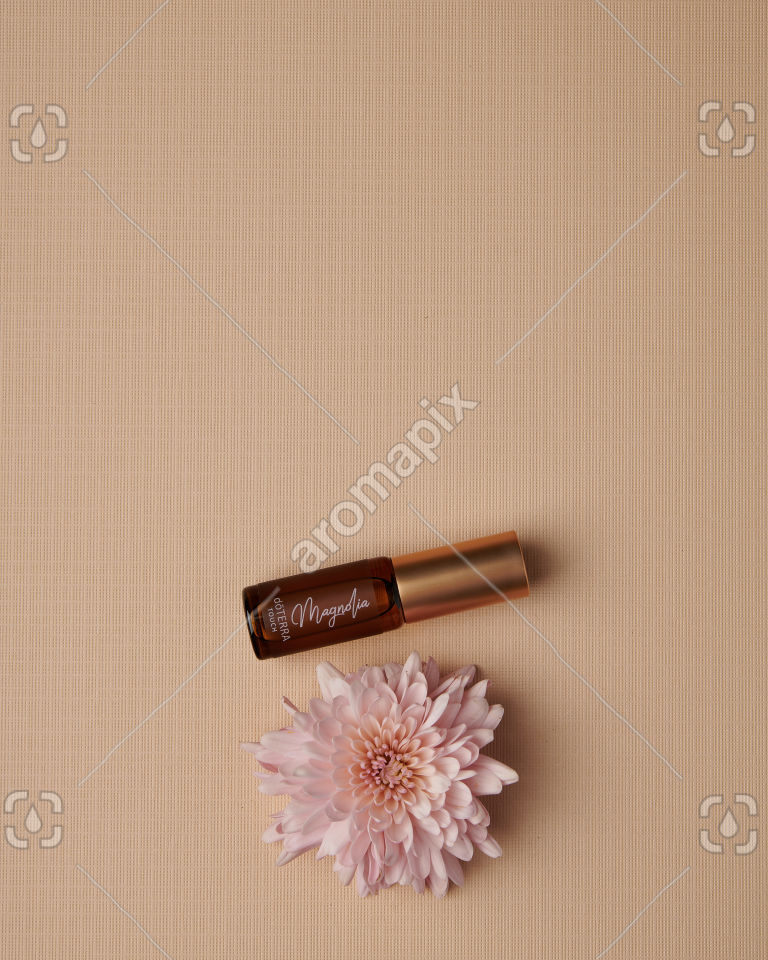 doTERRA Magnolia Touch 4ml with a pink flower on tan