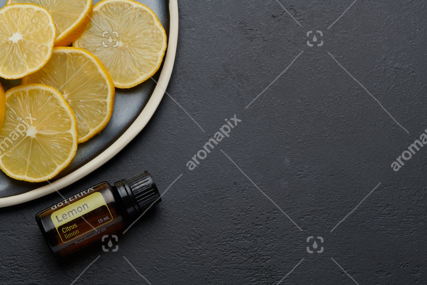 doTERRA Lemon product and slices on blue plate