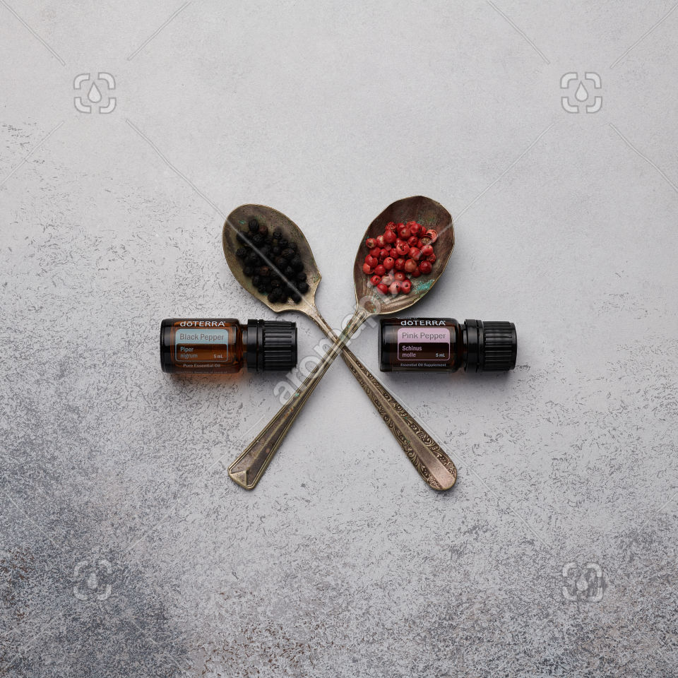doTERRA Black Pepper and Pink Pepper with black and pink peppercorns on white