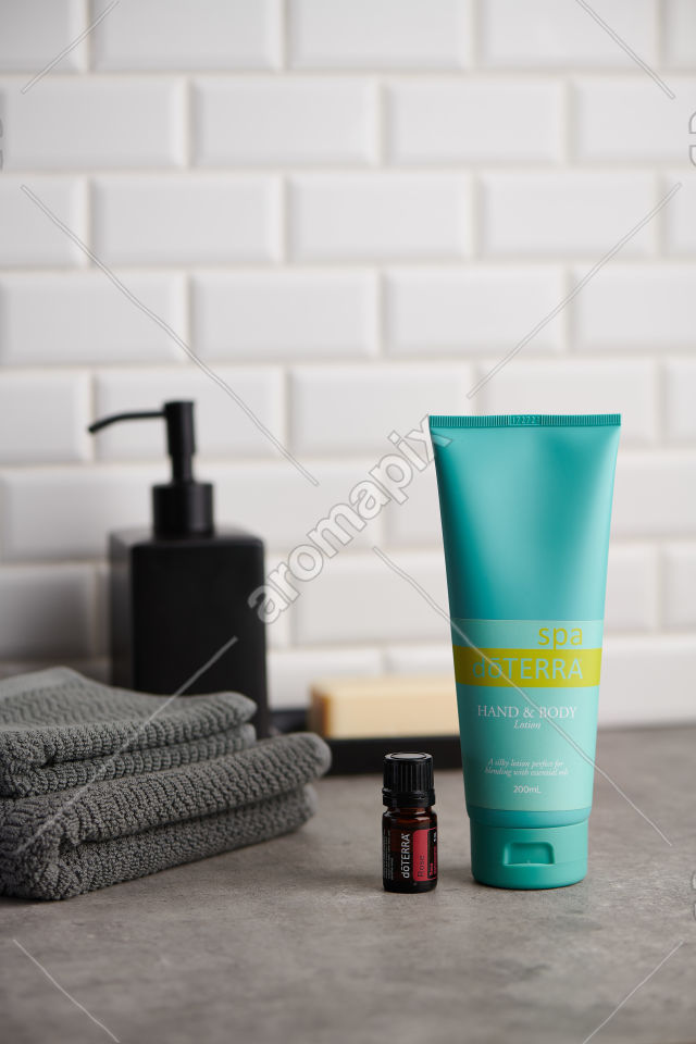 doTERRA Spa Hand and Body Lotion and Rose essential oil on stone bench